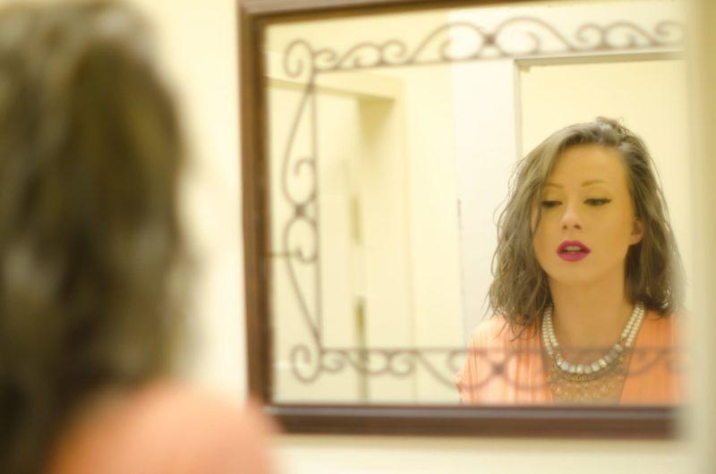 鏡で自分の顔を見ている外国人女性