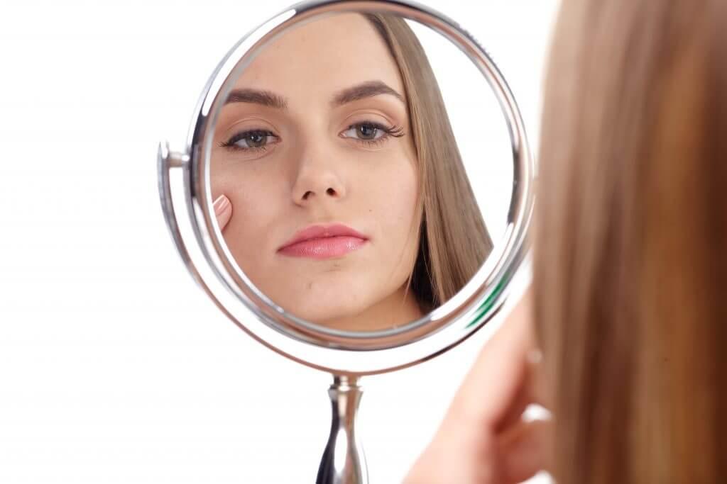 鏡で肌を確認している女性