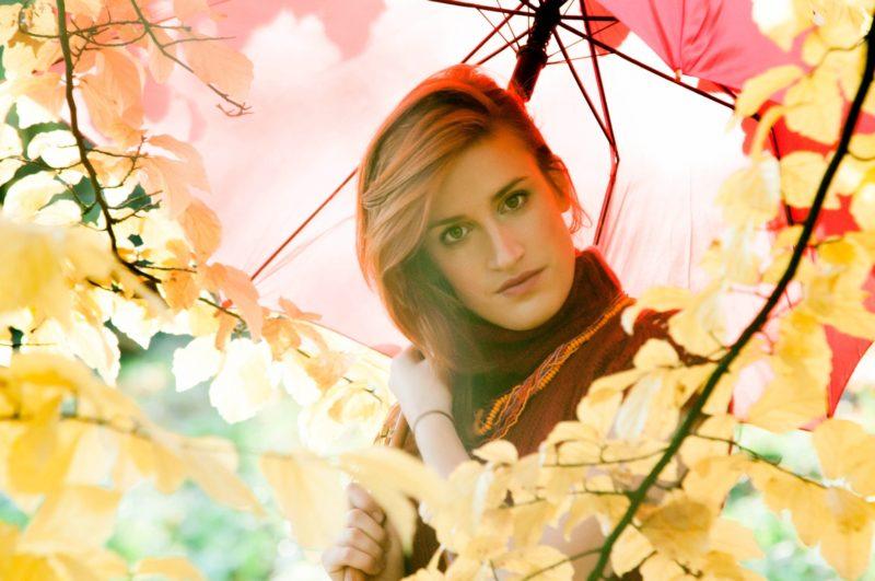 紅葉した木と傘を持った女性