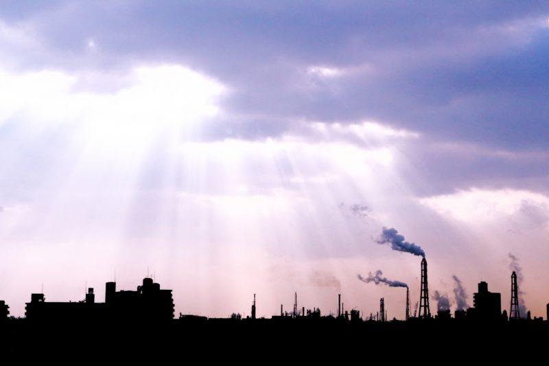 雲の隙間から降り注ぐ光と工場