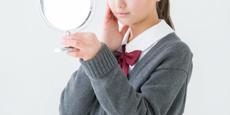 鏡を見て肌に手を触れる女の子