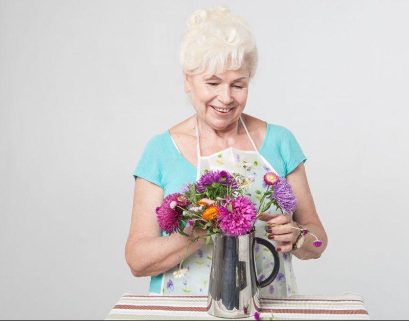 花瓶に花を生ける年配の女性