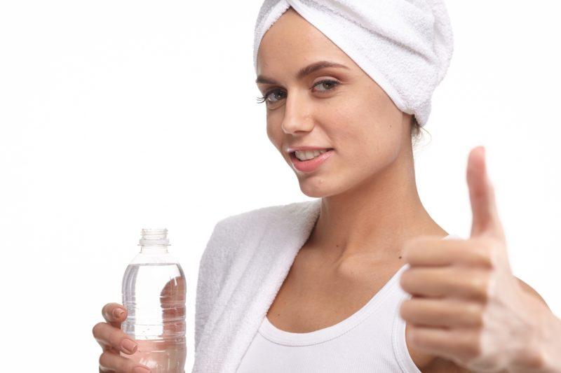 水の入ったペットボトルを持つ女性