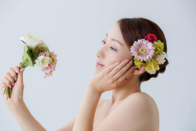 花束を持って頬に手を当てる女性