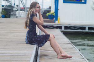 桟橋に座る青いドレスの女性
