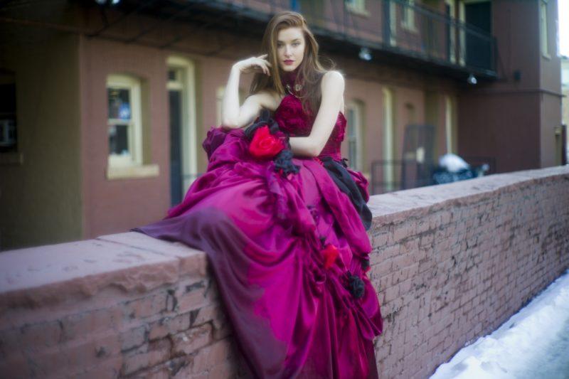 塀に寄り掛かる赤いドレスの女性
