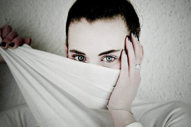 布で半分顔を覆った女性