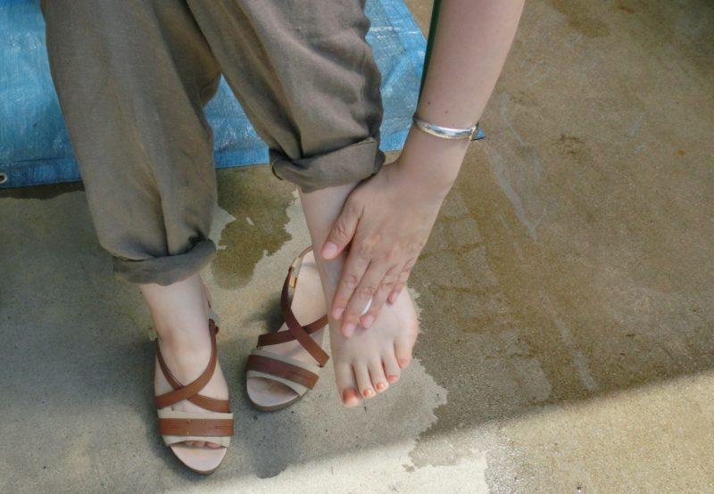 日焼け止めを足に塗る女性