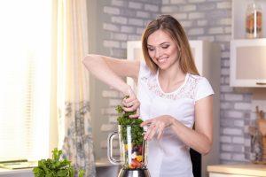 ミキサーに野菜を入れる女性