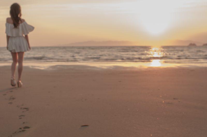 海に沈む夕日と少女
