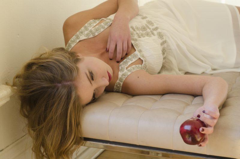 リンゴを持って横になっている女性