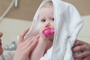 タオルを被りおもちゃを咥える赤ちゃん