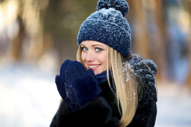 雪の日に手の平を温める女性