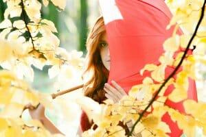 赤い傘で顔の半分を隠す女性