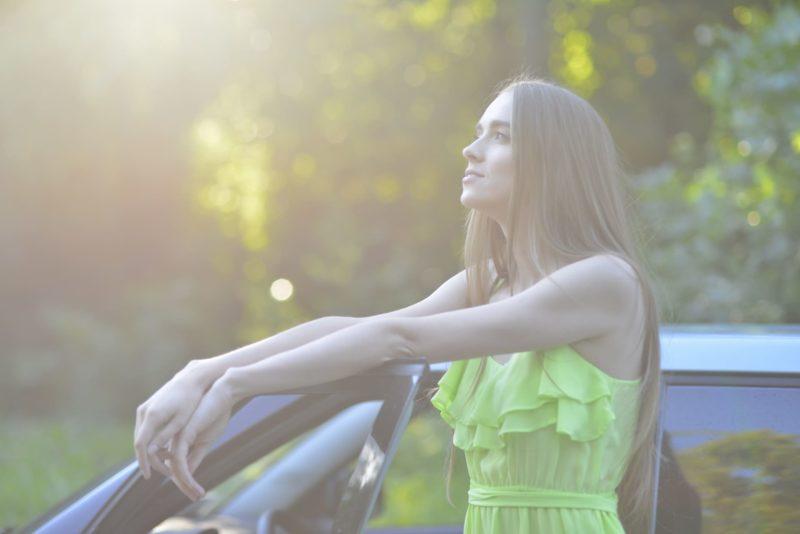 車の隣に立つ外国人女性