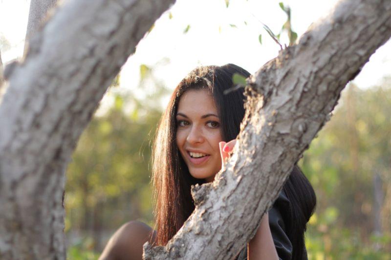 木の隙間から顔を覗かせている女性