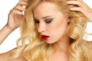 髪を触れている金髪の女性