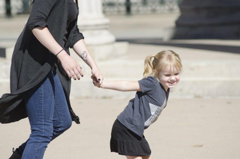 大人の手を引っ張る金髪の子供