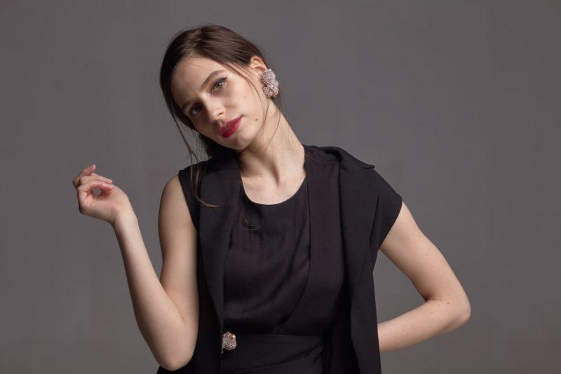 首を傾げている黒い服を着用している女性