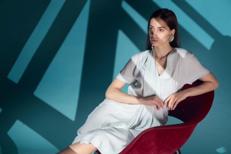 椅子に腰かけている白い服を着用している女性