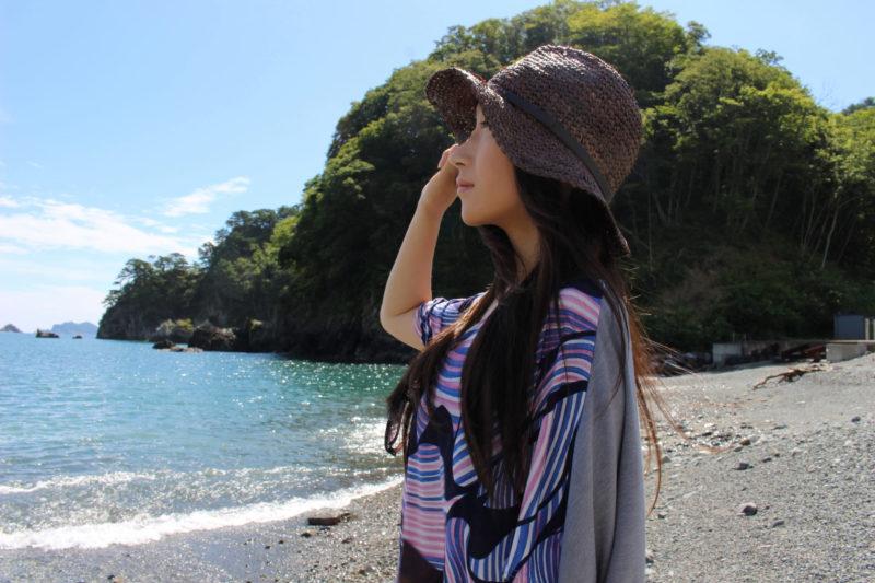 海にいる帽子を被った女性の画像