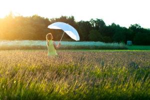 ラベンダー畑にいる傘を持った女性