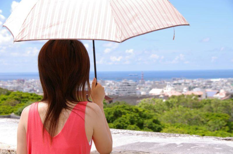 日傘を差しているノースリーブの女性