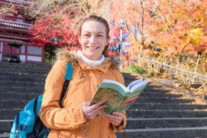 紅葉のお寺を散策している女性が次はどこ行こうかと計画を練っているとこ