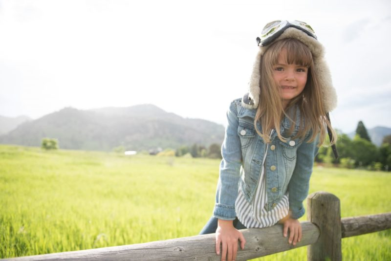 牧場で帽子をかぶっているジージャン姿の女の子