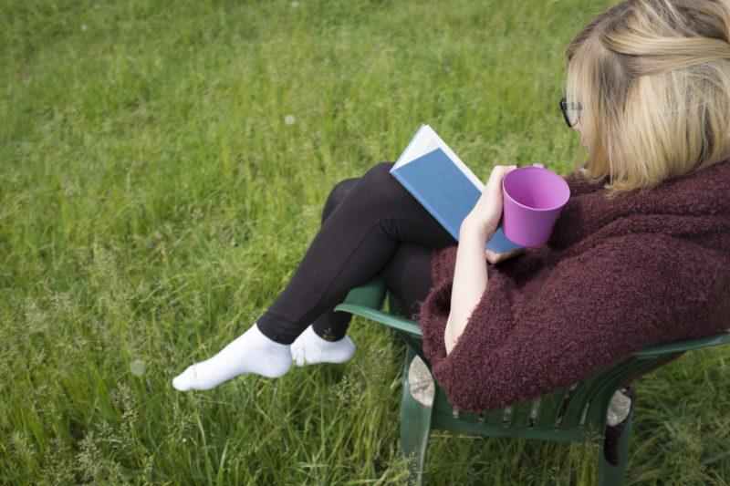 草原でカーディガンを着ながらカフェしている女性