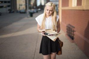 本をたくさん持って考え込んでいる女性