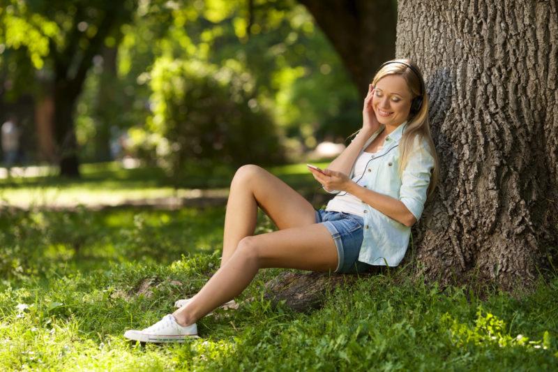 木々の中で音楽プレーヤーでリラックスしている女性