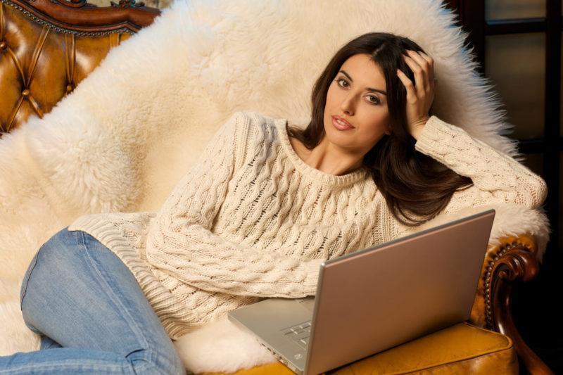 ソファに寝そべってパソコンを見ている女性