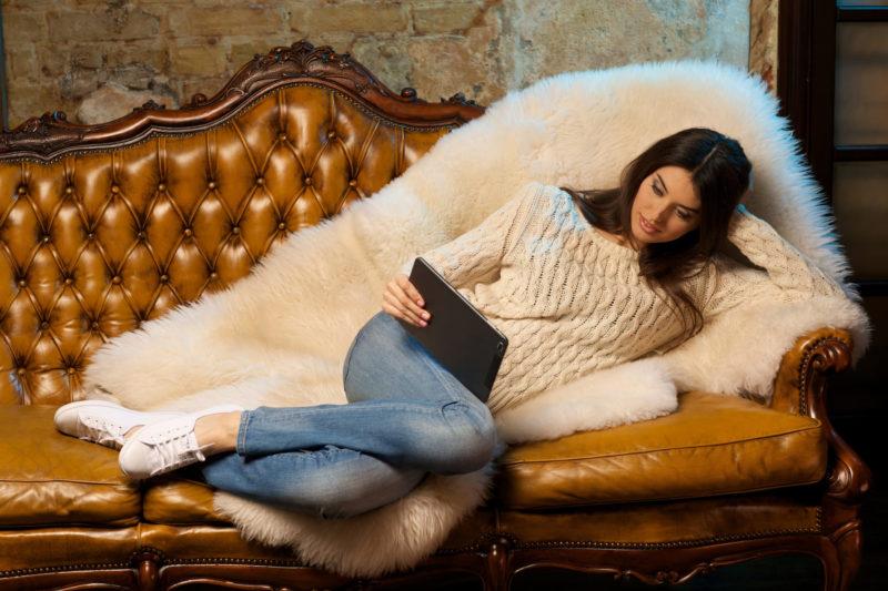 ソファでタブレットで情報を眺めている女性