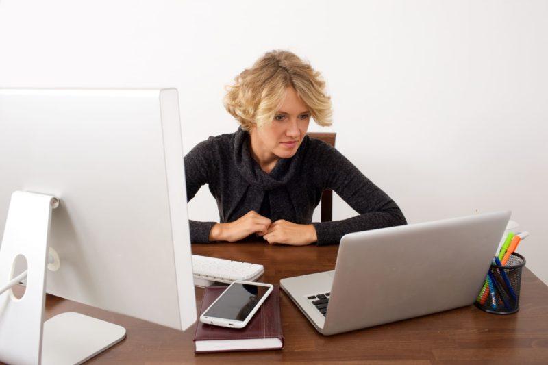 パソコンを見比べている女性