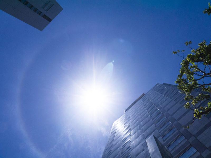 ビルとビルの間に太陽の光が差し込む写真