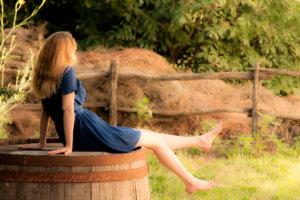 樽に腰かけている女性の画像