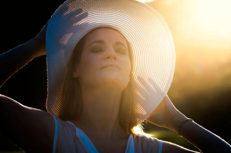 帽子に手を当てる外国人女性