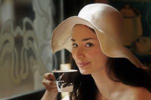 帽子を被ってカップで飲み物を飲む女性