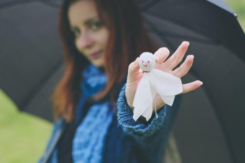 傘を差しながらてるてる坊主を持つ外国人女性