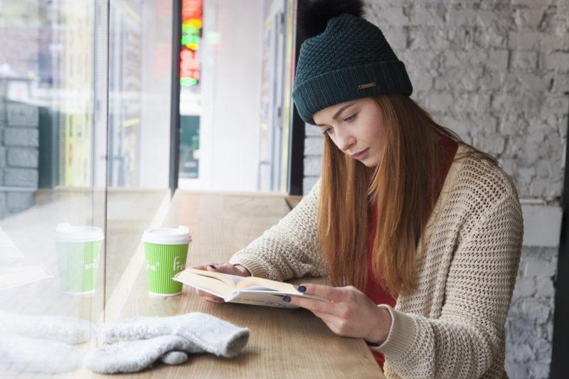 カフェで本を読むニット帽の外国人女性