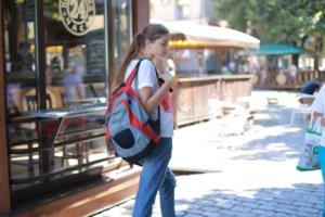 リュックサックを背負いながら街を歩く外国人女性