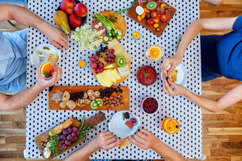 フルーツを食卓(テーブル)で食べている人々の画像