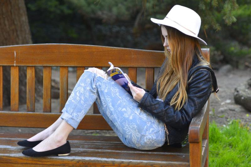 ベンチで雑誌を読む白い帽子の女性