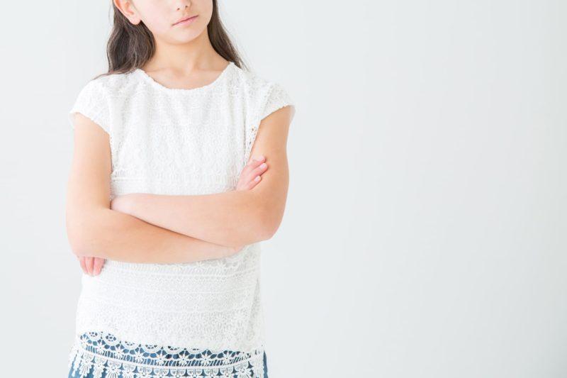 腕を組み、考える様子の女の子