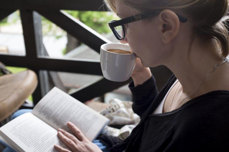 ティータイム中に読書する女性