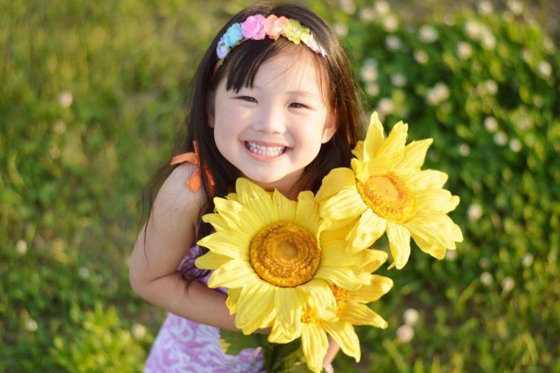 向日葵を持って満面の笑みをたたえている少女