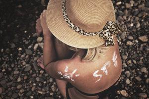 日焼け止めで背中に文字を書く帽子を被った外国人女性