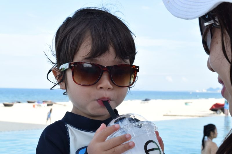 サングラスをかけて海でシェイクを飲む子ども