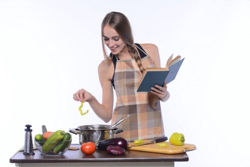 レシピ本を片手に料理をする外国人女性